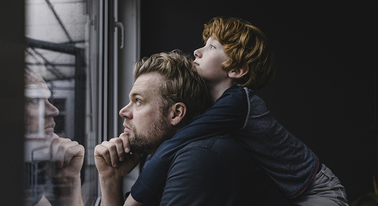 Father and son looking out of window on rainy day